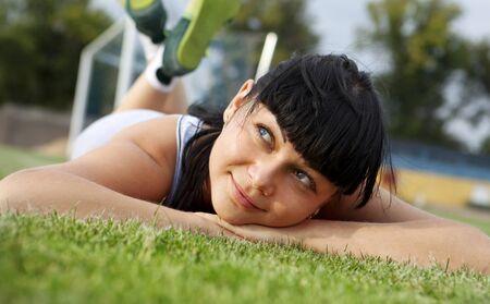 closeup of beautiful dreamy woman face that lies on grass