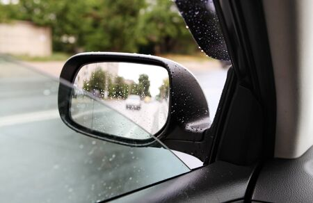 car driving on empty road, rear-view mirror in rainy weather Banco de Imagens