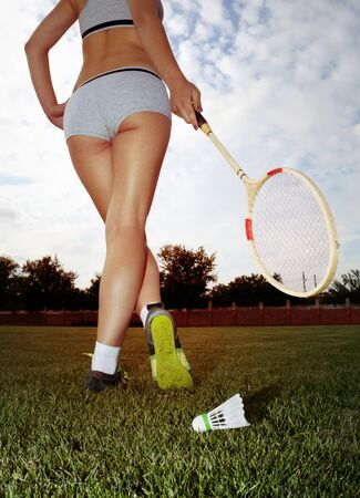 playing field: long legs of woman who plays badminton on grass