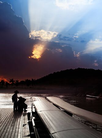shallop: locals on pier and sky over Khwae Yai river Stock Photo