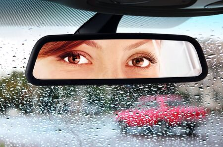 women face stare: woman sits on drivers seat and Looks in the rear-view mirror