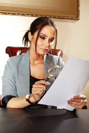 searcher: business woman looks on one document by magnifying glass