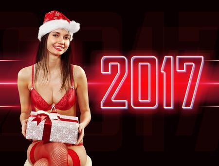 señora: Santa-muchacha joven atractiva en bikini rojo con el presente en el fondo 2017