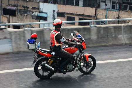 BANGKOK, THAILAND - DECEMBER 23: An unidentified traffic police officer rides a motorbike on a city street on December 23, 2013 in Bangkok, Thailand. Police patrols on motorbike are commonplace in the Thai capital. Editorial