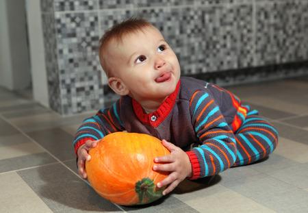 little boy of eight months holding not big orange pumpkin Stock Photo