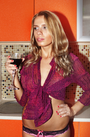 sad beautiful woman in kitchen with glass of wine