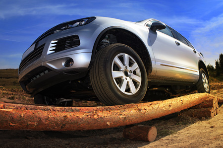SUV overcomes the obstacle built from wooden logs Stock Photo