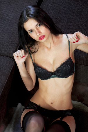 voluptuosa: voluptuosa chica sexy en ropa interior en el sofá obtiene placer Foto de archivo