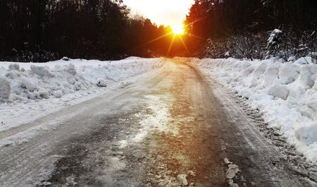 smother: Snow covered winter road with shining streetlights  in rural areas at sunset
