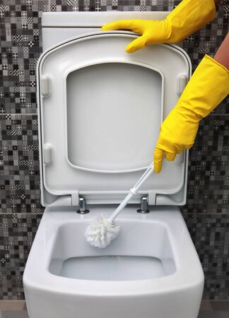 rubber gloves: cleaning of toilet bowl in yellow rubber gloves