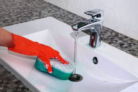 hand of woman in glove who washes white sink Stock Photo