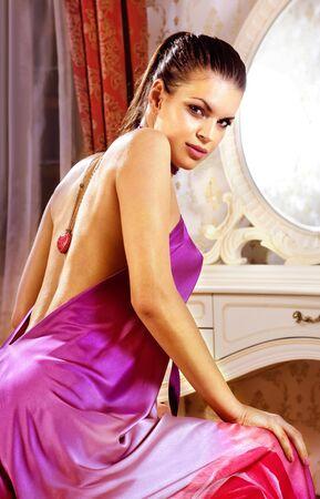 luxury hotel room: woman wearing long dress in her room of luxury hotel Stock Photo