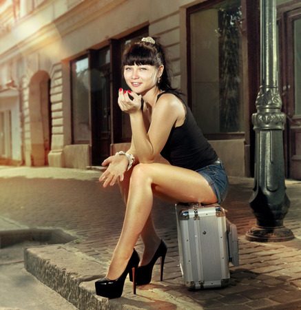 woman sits on suitcase near road in small ancient city Stock Photo