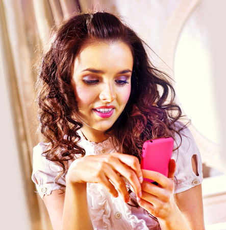 luxury hotel room: beautiful lovely woman with smartphone in luxury hotel room