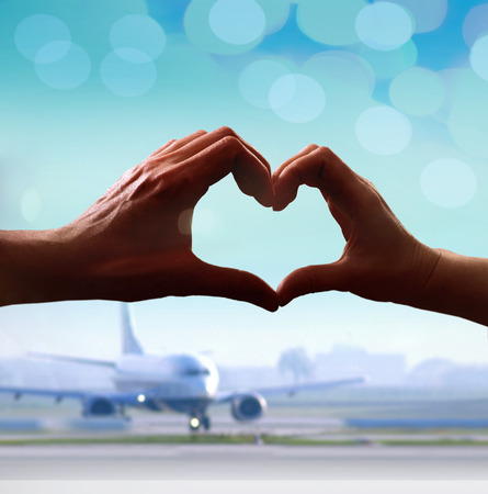 Silhouette of hands in form of heart when sweethearts have touched at airport photo