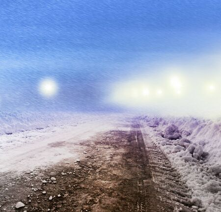 turnpike: Snow covered winter road with shining streetlights at night