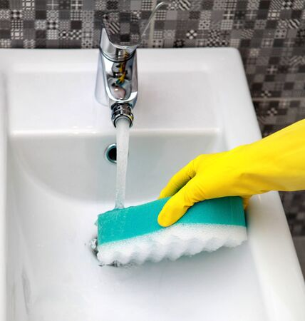 hygienic: Hand in yelow glove with sponge washes sink