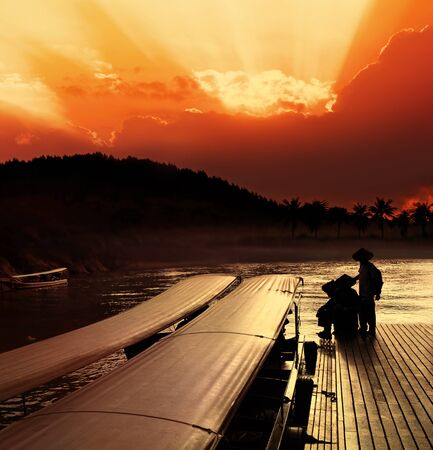 shallop: Taxi boats that use in Thailand on Khwae Yai river. Mooring at sunset Stock Photo
