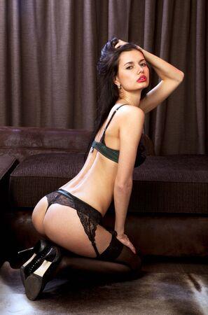 prostituta: voluptuosa chica sexy en ropa interior negro obtiene placer en el sofá