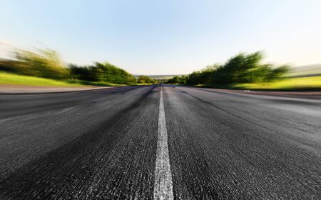 speedway park: asphalt road through the green field in summer day Stock Photo