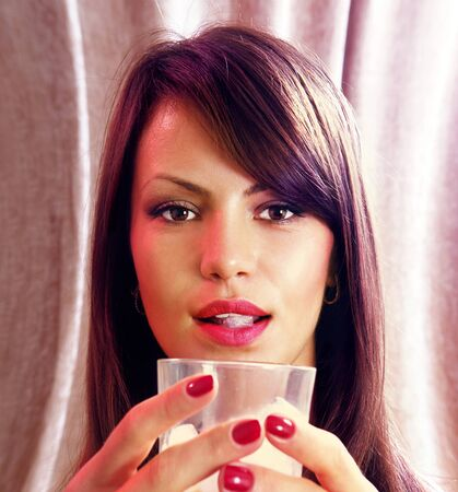 beautiful face of woman with glass of whisky photo