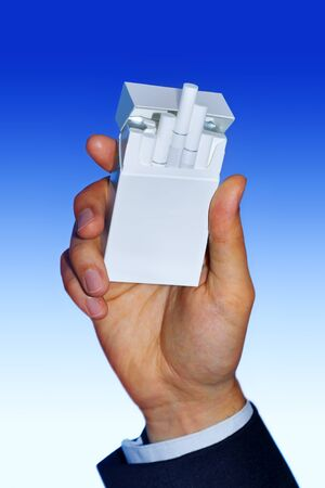 white pack of cigarettes on male hand photo