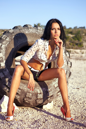 the beautiful girl poses on a tire in desert at hot day Stock Photo