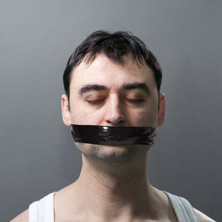 man's portrait with black duck tape on his face photo