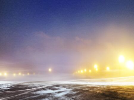 Snow covered winter road to airport at night Stock Photo