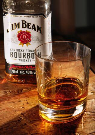 LVIV, UKRAINE - DECEMBER 04: Bottle of Jim Beam whisky and glass on wooden shelf on December 04, 2017 in Lviv