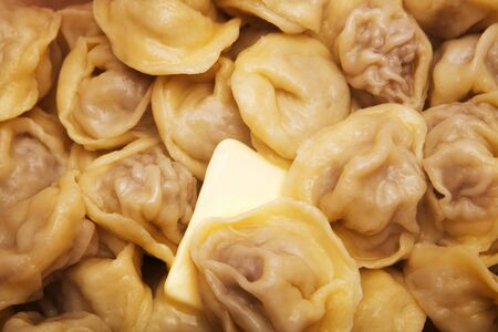 close-up of hot cooked dumplings with a slice of butter, poor quality food