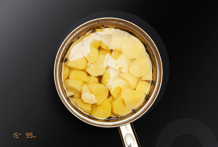 pan on the induction surface in which potatoes is cooked Stock Photo