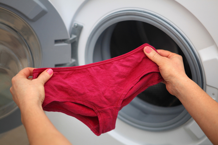 women's shorts in hands of woman who is going to do laundry it in washing machine Foto de archivo