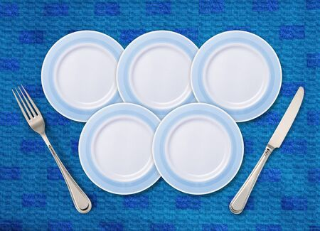 Five white plates on restaurant table that is  placed with knife with fork.