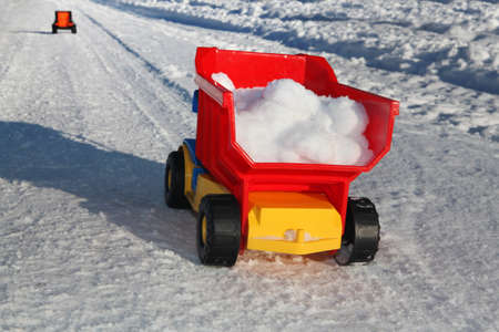 toy truck removes snow on the road in winter