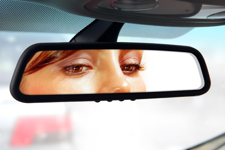 woman sits on drivers seat and Looks in the rear-view mirror