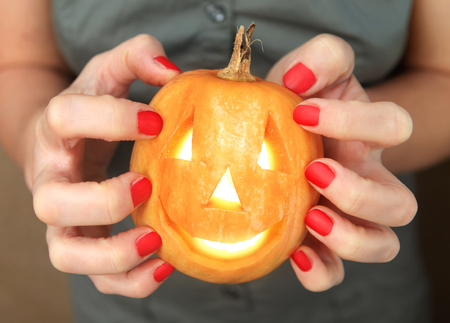 small yellow pumpkin in hands during the celebration Halloween
