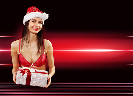 Beautiful Santa girl in red bikini with present on red background