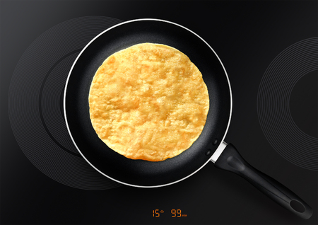 black frying pan with pancake on induction plate Stockfoto