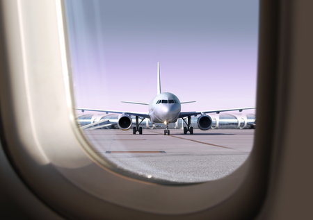 passenger airplane on runway of airport, view   through a window