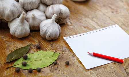 blank for recipe or note with pensil on wooden surface with garlic and spices Stockfoto