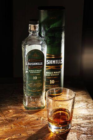 LVIV, UKRAINE - DECEMBER 04: Bottle of Bushmills whisky and glass on wooden shelf on December 04, 2017 in Lviv