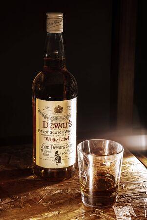 LVIV, UKRAINE - DECEMBER 04: Bottle of Dewars whisky and glass on wooden shelf on December 04, 2017 in Lviv