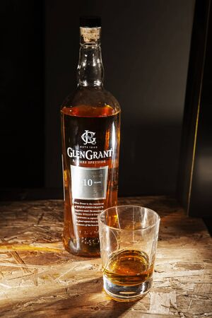 LVIV, UKRAINE - DECEMBER 04: Bottle of Glen Grant whisky and glass on wooden shelf on December 04, 2017 in Lviv