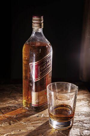 LVIV, UKRAINE - DECEMBER 04: Bottle of Johnnie Walker whisky and glass on wooden shelf on December 04, 2017 in Lviv 新聞圖片