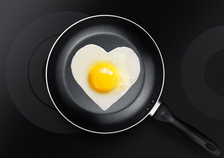 festive snack made of fried egg in the form of heart on frying pan for Valentines Day
