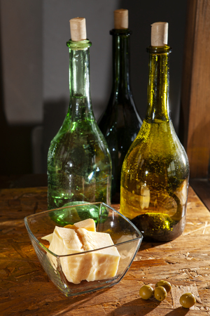 three bottles of olive oil and parmesan cheese on a wooden surface