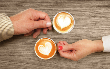 hands of lovers which hold cups of coffee on table