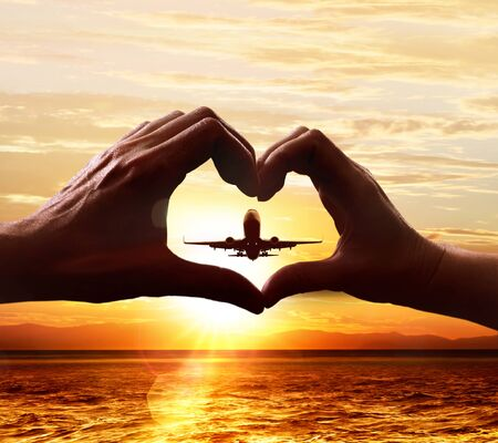 Hands of lovers in the form of heart, which against the background of the sky with the taking-off plane Stockfoto