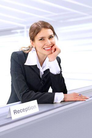 beautiful receptionist stands near the desk in hotel